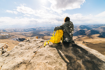 woman tourist sits on a background of high mountains