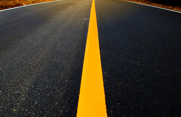 Yellow solid line. Road markings on asphalt on the street.