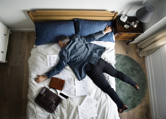 Exhausted business man falling asleep as soon as he came back home Wall mural
