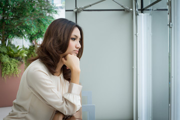 absent minded, stressed, unhappy sad woman looking out ot the office window
