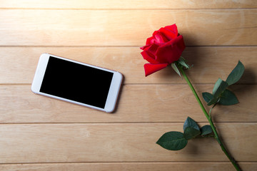 Red rose and Phone on the old wood. valentine concept.