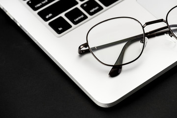 Closeup of eyeglasses on computer laptop