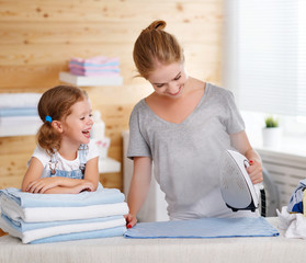 Happy family mother housewife and child daughter ironing clothes   in laundry
