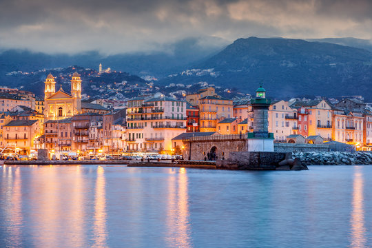 Bastia, a beautiful city landscape, a port with boats, a sunset and the lights of a night city. France, Corsica, a popular destination for travel in Europe