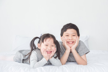 Asian boy and girl lying on bed and smile at camera