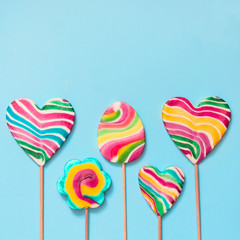 Set of five rainbow colorful lollipops isolated on blue background.