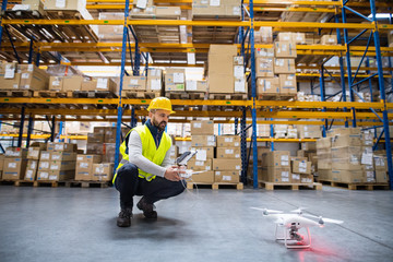 Man with drone in a warehouse.