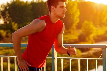 Young man running on bridge at sunset.