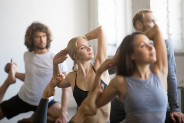 Group of young sporty people practicing yoga lesson with instructor, stretching in Mermaid exercise, Eka Pada Rajakapotasana pose, working out, indoor close up, students training in club, studio