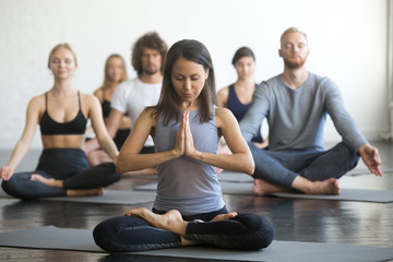 Group of young sporty people practicing yoga lesson with instructor, sitting in Padmasana exercise, Lotus pose with mudra gesture, working out, students training in club, indoor full length, studio