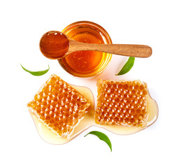 Honeycomb with jar and honey spoon and leaf isolated on white background