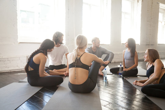 Group of young sporty people relaxing sitting in circle after workout. Enjoy pleasant effective communication, allowing body to recover to avoid overworking in gym, indoor studio. Wellbeing concept