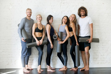 Portrait of young sporty people standing at the wall looking at camera. Group of fitness students enjoy each other company, making friends in yoga community, resting after lesson. Indoor full length