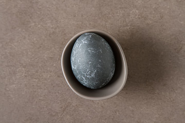 Easter composition with gray eggs on a colored background, space for text