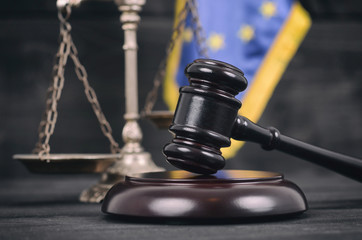 Scales of Justice, Judge Gavel and Flag of the European Union on a wooden background.