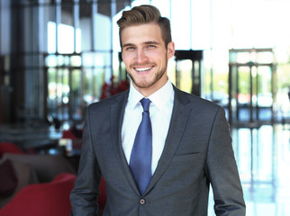 Portrait of happy young businessman standing in hotel lobby.