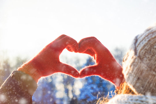 Women's Hands in Red Glove Folded in Heart Shape. Winter Concept. Snowfall