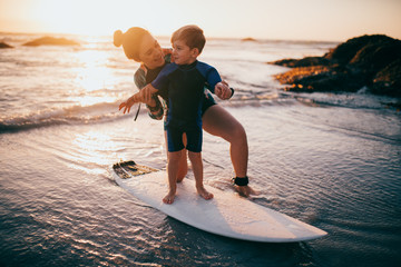 Little boy and mother surfing at beach