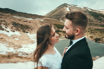 Young couple wedding,looking at each other in the eyes, against the lake and the mountains, tilt-shift effect