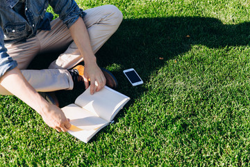 Student reads a book sitting on the green lawn before the modern library
