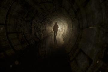 Mann läuft mit Taschenlampe durch Abwassertunnel