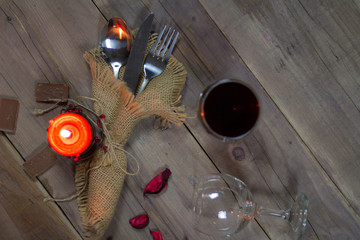 Romantic table setting valentines day background. Chocolate, wine, rose petals,and candle