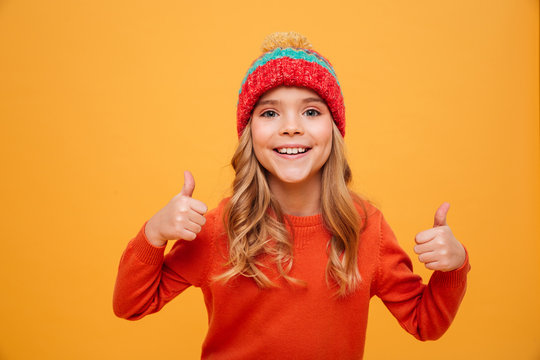 Happy Young girl in sweater and hat showing thumbs up