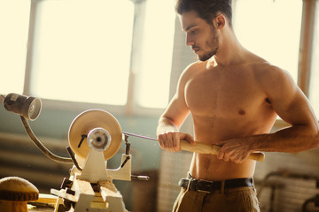 naked man carpentering in workshop and using small manual lathe
