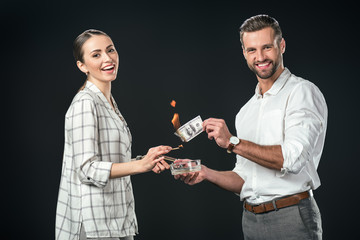 smiling man and woman burning dollar banknotes, isolated on black