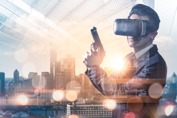 The double exposure image of the businessman hold a gun during sunrise overlay with cityscape image. the concept of virtual hologram, simulation, gaming, internet of things and future life.