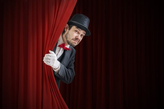 Nervous actor or illusionist is hiding behind red curtain in theater.