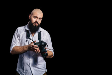 Bearded photographer takes a photo. Close up. Black background