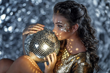Portrait of young woman with disco ball in hands.