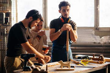 Carpenter showing apprentice how to use sawing machine