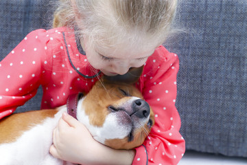 Little blonde curly girl hugging a basenji dog.