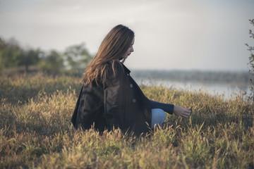 Thoughtful sad, melancholic girl sitting in the grass, running through her memories Wall mural