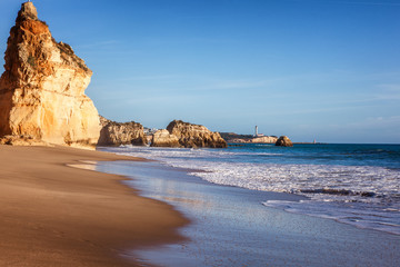 Beautiful ocean landscape, the coast of the Atlantic Ocean, Portugal, the Algarve. Blue ocean, cloudless sky, yellow rocks