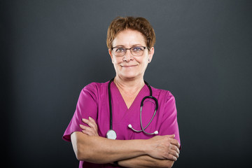 Portrait of senior lady doctor standing with arms crossed