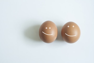 Two eggs on a white background. Eggs with a smile.