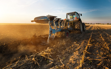 Tractor plowing fields -preparing land for sowing in autumn Wall mural