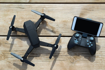 Black Drone quadcopter with a remote control and phone on wood table