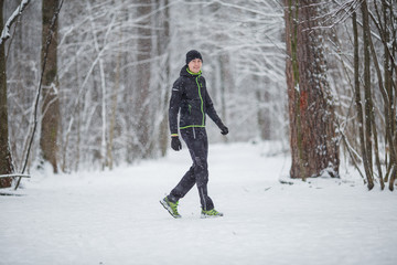 Photo of man in sports clothes on run in winter