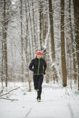 Photo of man in sportswear, red cap on run in winter