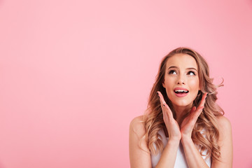 Portrait of happy blonde woman looking upward and gesturing hands in delight, isolated over pink background copy space