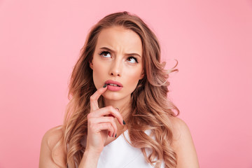 Image closeup of attractive woman with blondy curls thinking hard while putting finger at lips and looking upward, isolated over pink background
