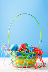 Photo of basket with colorful eggs