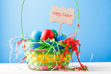 Photo of basket with colorful eggs with wish of happy Easter