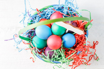 Image on top of basket with colorful eggs on wooden table
