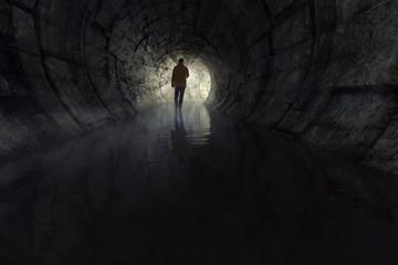 Mann mit Taschenlampe in Abwasserkanal