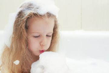 Little blonde girl in bath blowing on the foam.